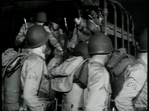 vídeos de stock, filmes e b-roll de line of parked transport trucks filled w/ us army soldiers in train depot ms soldiers getting out of truck small group of mps standing talking night... - 1943