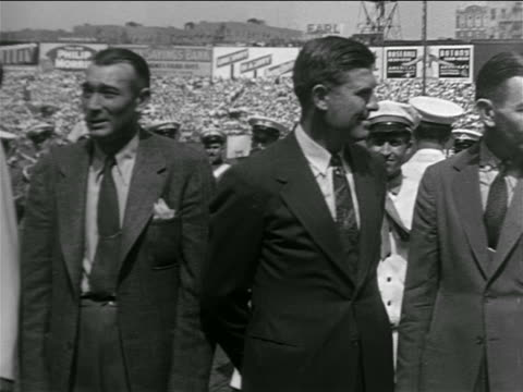 stockvideo's en b-roll-footage met pan line of past yankees players in suits in crowded stadium for lou gehrig's farewell - compleet pak