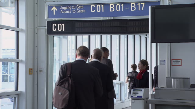 stockvideo's en b-roll-footage met ms line of people having tickets checked at airport boarding gate/ zi late man arriving at gate and running down corridor/ munich, germany - münchen vliegveld