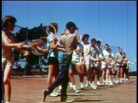 1957 line of people practicing swinging with tennis racquets outdoors / educational - tennis stock-videos und b-roll-filmmaterial