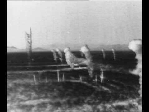 line of people silhouetted in foreground in early dawn as cloud of smoke from atomic detonation stands in background as part of blast test / montage... - radioaktiver niederschlag stock-videos und b-roll-filmmaterial