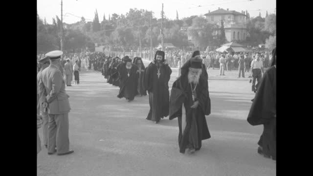 line of people walking towards panathenaic stadium / line of people walking towards stadium, line of greek orthodox priests walking parallel to them... - grecia stato video stock e b–roll