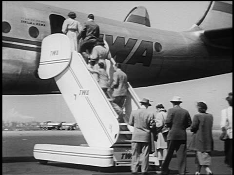 B/W 1951 REAR VIEW line of people walking up stairs + entering TWA airliner outdoors