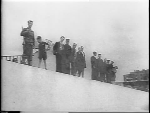 line of people watches from top of wall / montage of soldiers inspecting coffins of torture victims at mass gravesite - anno 1944 video stock e b–roll