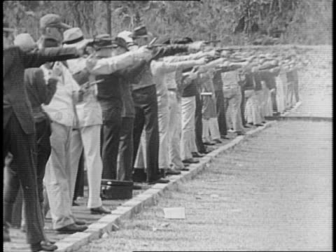 vídeos y material grabado en eventos de stock de line of pistol match competitors ready to fire pistols at target / competitors begin firing / two men short at targets with clear accuracy / balloons... - satírico