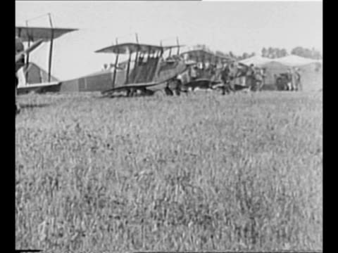vídeos de stock, filmes e b-roll de line of planes stands in field in des moines, ia / men load bundle of newspapers into one pilot's seat as two pilots sit in plane / plane flies over... - publicação