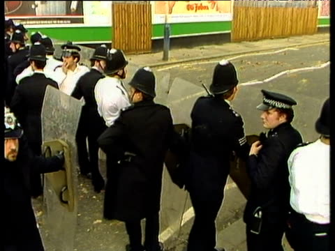 line of police officers stand in road behind riot shields pan up to plumes of black smoke from burning vehicles in distance brixton; apr 81 - 1981 stock videos & royalty-free footage