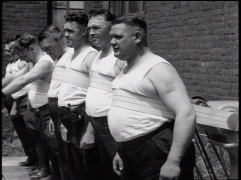 stockvideo's en b-roll-footage met b/w 1935 line of policemen in tank tops standing with vibrating straps on bellies / newsreel - 1935