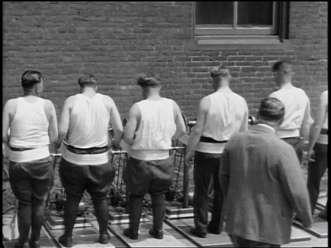 b/w 1935 rear view line of policemen in tank tops standing with vibrating straps on bellies / newsreel - 1935 stock videos & royalty-free footage