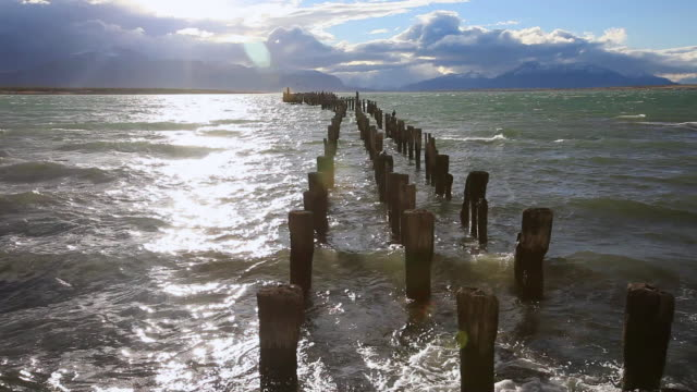 ws of line of posts remaining from old pier going into water with nice light mountains and clouds / puerto natales, chilean patagonia, chile - travelling light stock videos & royalty-free footage