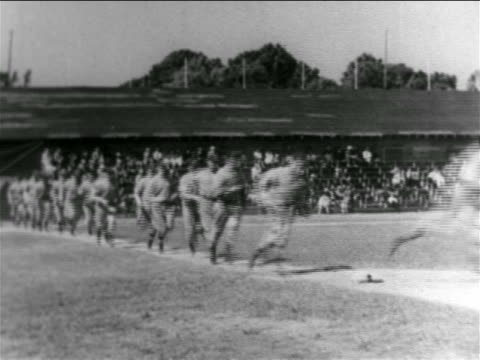 vídeos de stock e filmes b-roll de b/w 1938 line of professional baseball players running around bases on baseball diamond - camisola de basebol