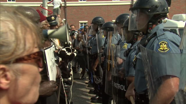 line of protesters stand in front of a line of police officers wearing riot gear in ferguson, missouri following the police shooting of michael brown. - 2014 stock-videos und b-roll-filmmaterial