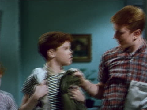1962 line of redheaded boys handing down pants from largest to smallest / industrial - retrokläder bildbanksvideor och videomaterial från bakom kulisserna