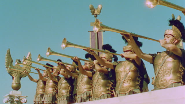 vídeos de stock, filmes e b-roll de line of roman soldiers blowing horns / quo vadis (1951) - roman soldier
