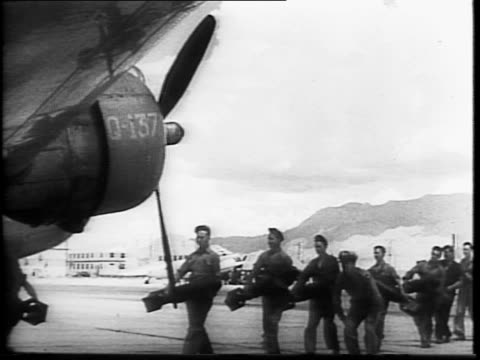 line of soldiers carrying bombs to b-18 bomber plane / bombs being loaded into plane / soldier carry and load canvas bag into plane / exterior of... - new mexico stock videos & royalty-free footage