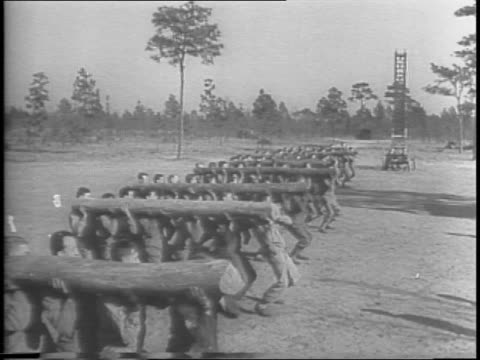 line of soldiers does elevated sit ups and pound their stomachs while other soldiers hold their feet / soldiers do inclined pushups on wood railings... - 自重トレーニング点の映像素材/bロール