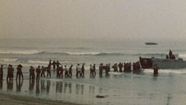A line of soldiers transferring military supplies from a vessel to the shore / Camp Pendleton California United States