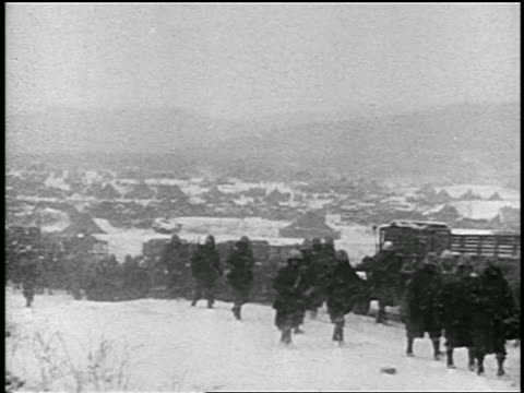 b/w 1951 line of soldiers walking in snowstorm during korean war / educational - 1951年点の映像素材/bロール