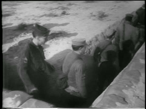 vidéos et rushes de pan line of soldiers walking into trench before hbomb explosion / yucca flats nevada - 1952