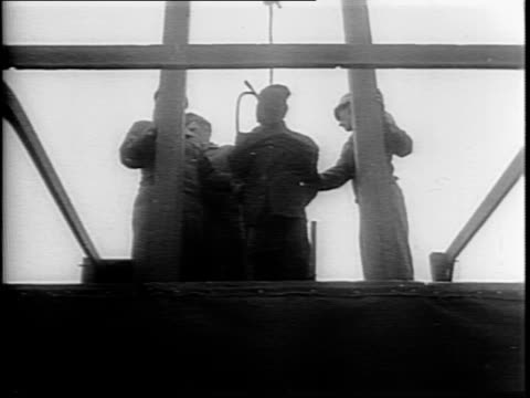 Line of soldiers watching execution / view of gallows with opened trap door / Johann Opper being led up to gallows by soldiers / low angle shot of...