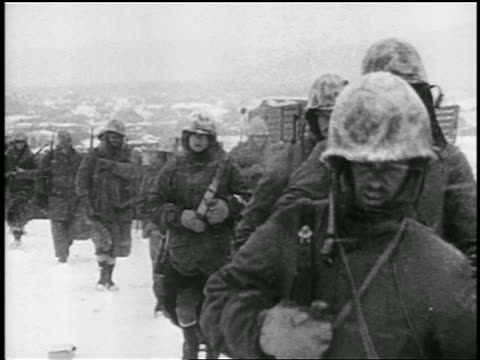 b/w 1951 line of soldiers with guns walking in snowstorm toward past camera / korean war / educ - 1951年点の映像素材/bロール