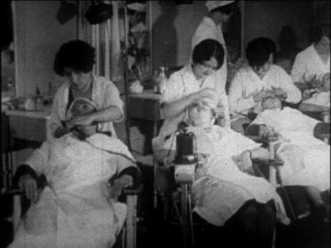 b/w 1926 pan line of students giving facials to women in beauty school / newsreel - 1926 stock videos and b-roll footage