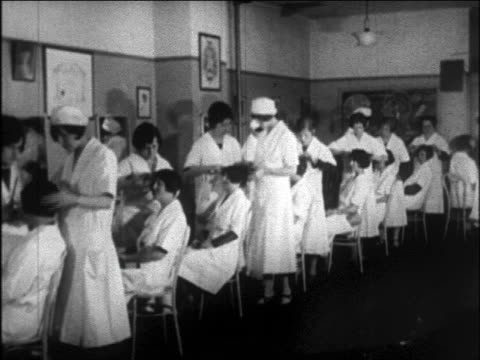 b/w 1926 line of students grooming women in beauty school / teacher checking on them / newsreel - 1926 stock videos and b-roll footage