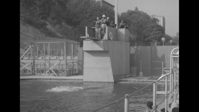 line of swimmers waits to dive off board on diving platform; lifeguard allows one at a time to dive off; first diver does a backflip, others just... - diving platform stock videos & royalty-free footage