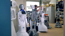 A line of tall robots await for a busy repairman to start fixing them. 4K.