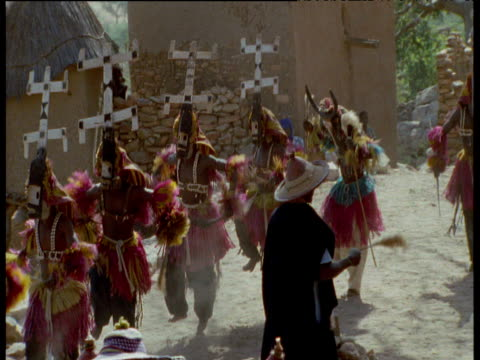 Line of tribal dancers in masks and headdresses as they perform a traditional funeral/remembrance dance, Mali