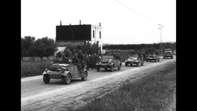 line of trucks carrying german prisoners drives by camera / german vehicle carrying german prisoners drives by crowd of german prisoners / german... - allied forces stock videos and b-roll footage