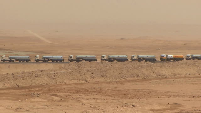 ws pov line of trucks on highway in desert, suez isthmus, egypt - trucks in a row stock videos & royalty-free footage