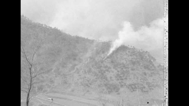 line of u.s. marines walk along a mountain trail in south korea. a plume of smoke is seen on a mountainside in the distance. - 1951 stock videos & royalty-free footage
