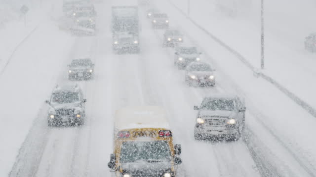 line of vehicles trudging through the winter storm - snow storm stock videos and b-roll footage