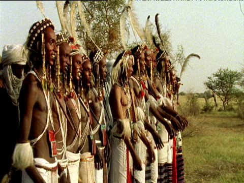 Line of Wodaabe tribesmen in feather headdresses and red make-up during courtship ritual Ingal Niger