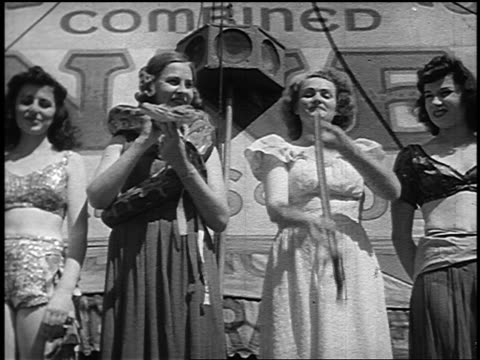 b/w 1946 line of woman outside of side show / one has snake around neck, another swallows sword - circus stock videos & royalty-free footage