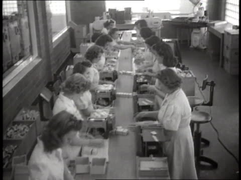 a line of women fill small boxes with bottles of penicillin then put the boxes on a conveyor belt - penicillin stock videos and b-roll footage