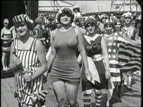 A line of women model swimsuits and swim caps during a fashion show