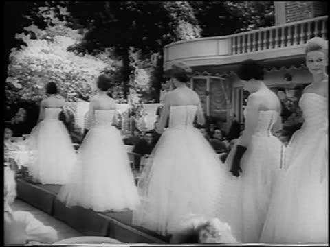 B/W 1960 line of women modeling evening dresses + gloves walking on runway outdoors / newsreel
