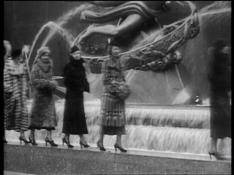 B/W 1936 line of women modeling fur coats on fountain ledge at Rockefeller Center, NYC
