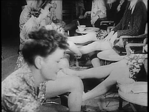 a line of women sit at beauty parlor / sign reads 'retouching two legs 3d' / montage of workers painting women's' legs / a line is drawn on the back... - exclusion stock videos & royalty-free footage