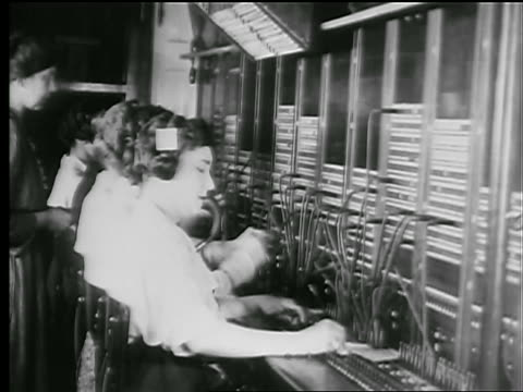 b/w 1927 profile line of women working at telephone switchboard / newsreel - 電話交換機点の映像素材/bロール