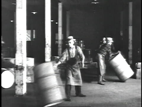 vídeos de stock, filmes e b-roll de 1929 montage line of workers rapidly moving barrels across plant floor / united states - 1920 1929