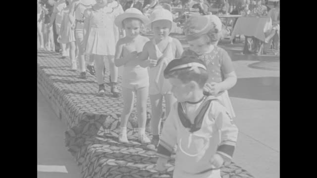line of young children parades along outdoor walkway led by boy in sailor suit and girl carrying tennis racquet / view from front of children... - sailor suit stock videos and b-roll footage