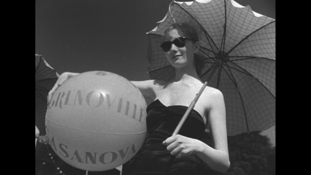 line of young women wearing black bathing suits and high heels hold beach balls and parasols as they stand at the edge of the fountain pool in the... - sonnenschirm stock-videos und b-roll-filmmaterial