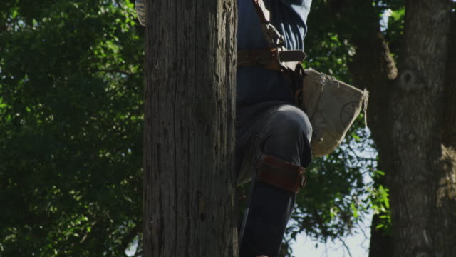 a line repair man climbs a wooden pole using gaffes and a safety harness. - safety harness stock videos & royalty-free footage
