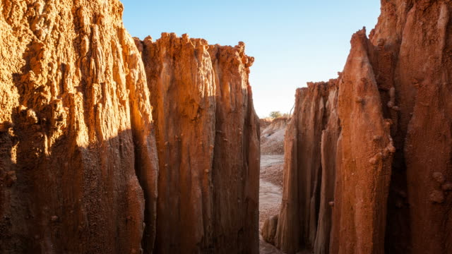 Linear pull-up abstract timelapse with eroded rock formations in the foreground, revealing a vast and dry landscape at sunset in Africa