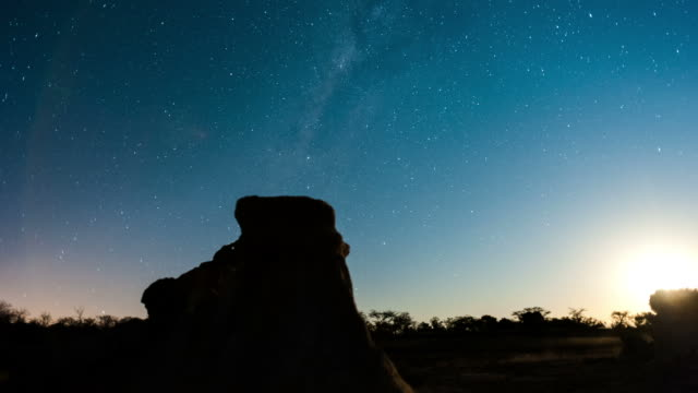Linear, push-in night timelapse of abstract landscape with silhouette eroded rocks while the moon is setting and the Milky Way moves into the frame
