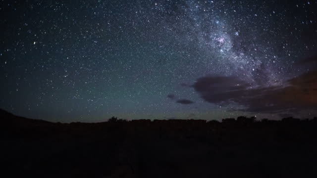 linear timelapse at nightfall from dusk into the night with the milky way rising and twisting through the sky, a few scattered clouds and greenish air glow and meteorites - old ruin stock videos & royalty-free footage