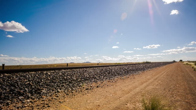 linear timelapse, right to left at 45 degree angle up of a typical karoo landscape with railway lines in a barren landscape, sun flare against a blue sky - karoo bildbanksvideor och videomaterial från bakom kulisserna